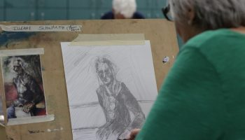 Older woman working on a pencil sketch based on a painted portrait with muted, dark colors.