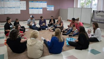 Parents and infants seated in a circle participating in a skill building activity