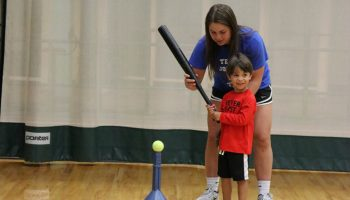 Teacher helping a child learn how to bat in tee-ball.