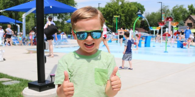 boy giving a thumbs up at the pool